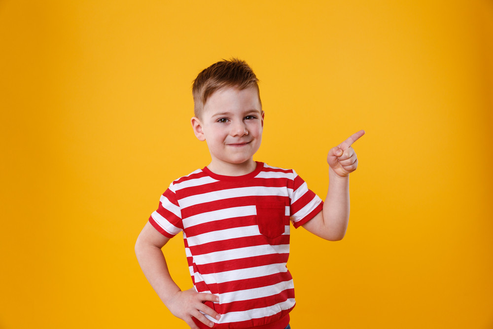 Smiling happy boy pointing finger away at copyspace isolated over orange background