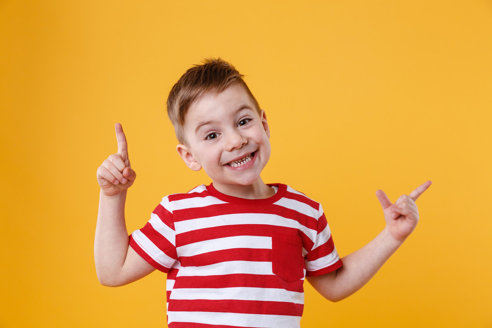 Smiling happy boy pointing fingers up at copyspace isolated over orange background