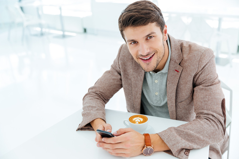 Smiling happy businessman holding smart phone and looking at camera indoors