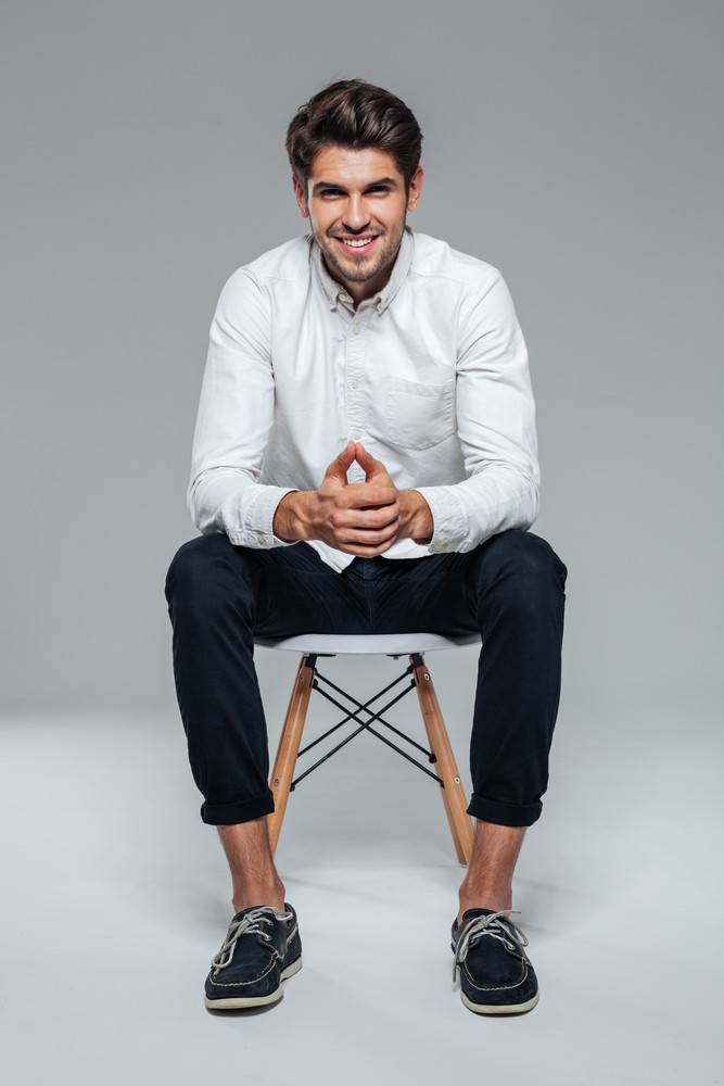 Smiling happy handsome man in white shirt sitting on the chair over grey background