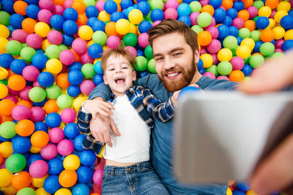 Smiling little boy and his father taking selfie in pool with colorful balls