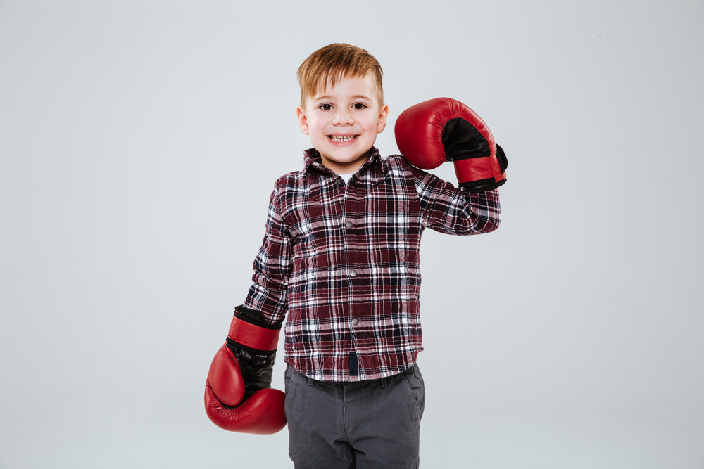 Smiling little boy in boxing gloves standing and showing biceps over white background