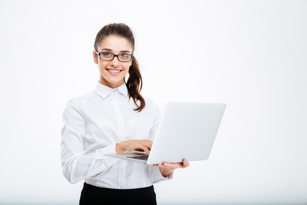 Smiling lovely young businesswoman standing and holding laptop over white background