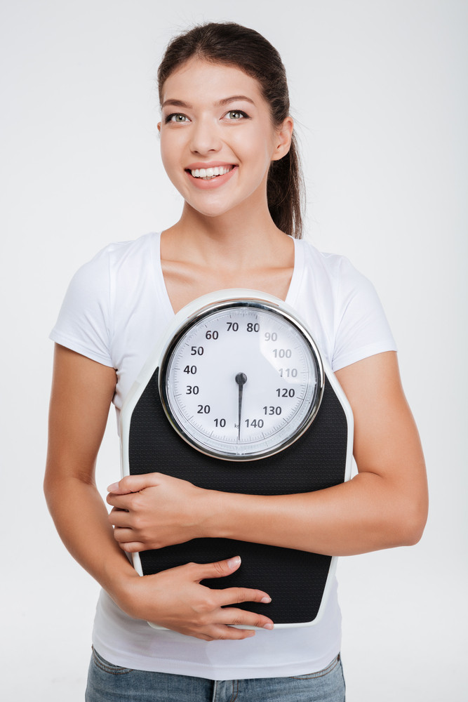 Smiling model in t-shirt with weight scale in studio. Isolated white background