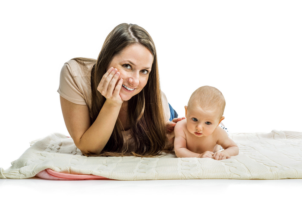 Smiling mother lying with her baby on a floor isolated on white background
