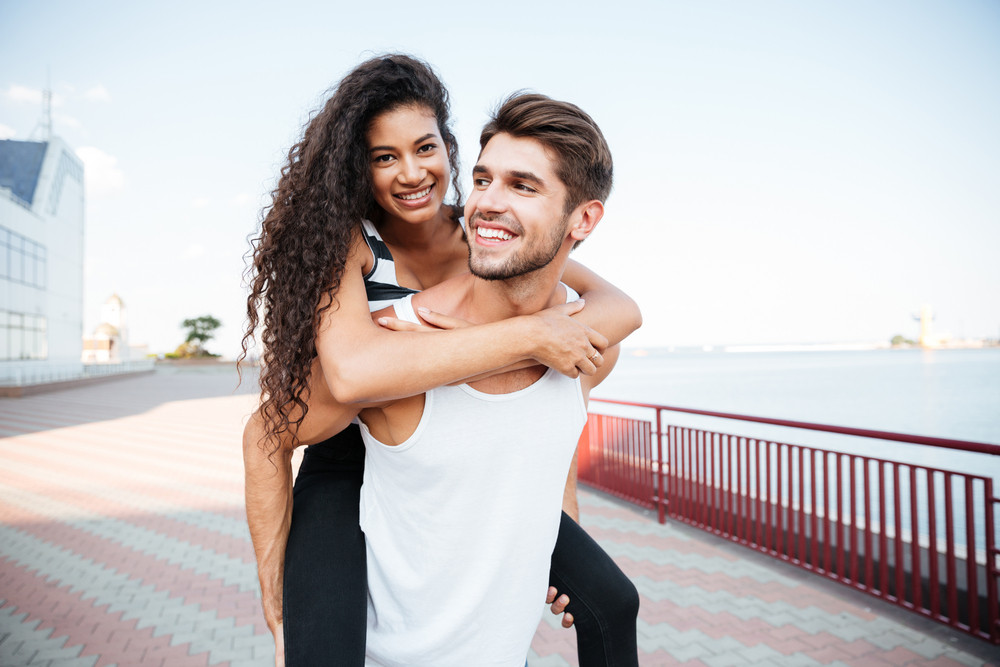 Smiling multiethnic young couple walking and having fun