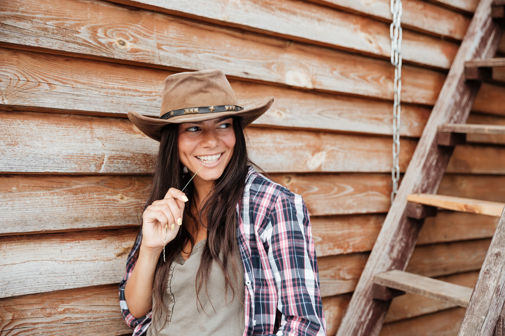 Smiling pretty young woman cowgirl in hat standing near the house