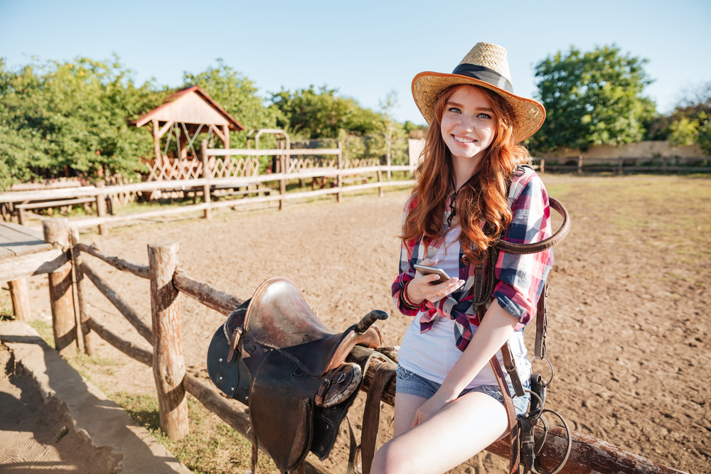 Smiling pretty young woman cowgirl standing and using mobile phone on ranch