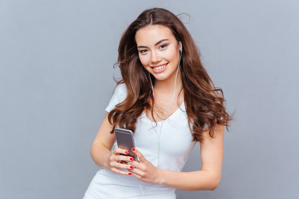 Smiling pretty young woman listening to music from smartphone isolated on a gray background