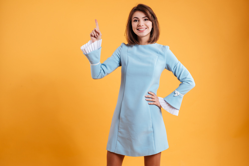 Smiling pretty young woman standing and pointing up over yellow background