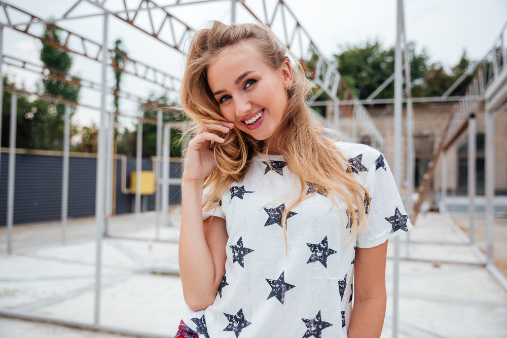 Smiling pretty young woman standing outdoors