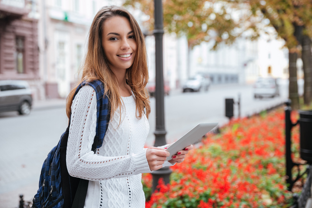 Smiling pretty young woman with backpack standing and using tablet in the city
