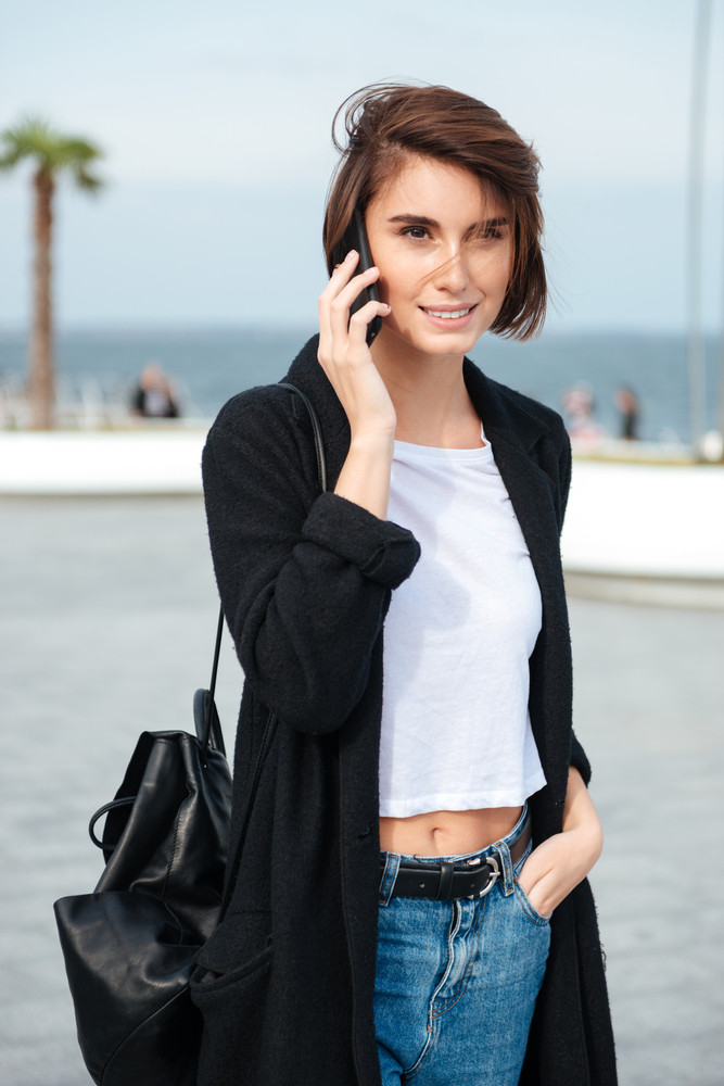 Smiling pretty young woman with backpack walking and talking on cell phone outdoors