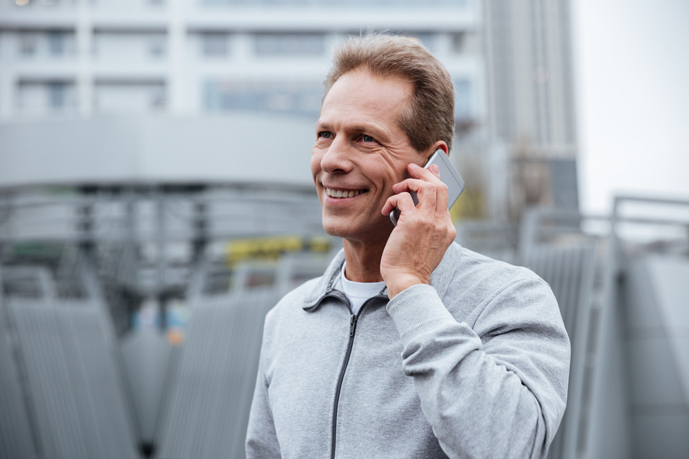 Smiling Runner in gray sportswear talking at phone on the street. Side view