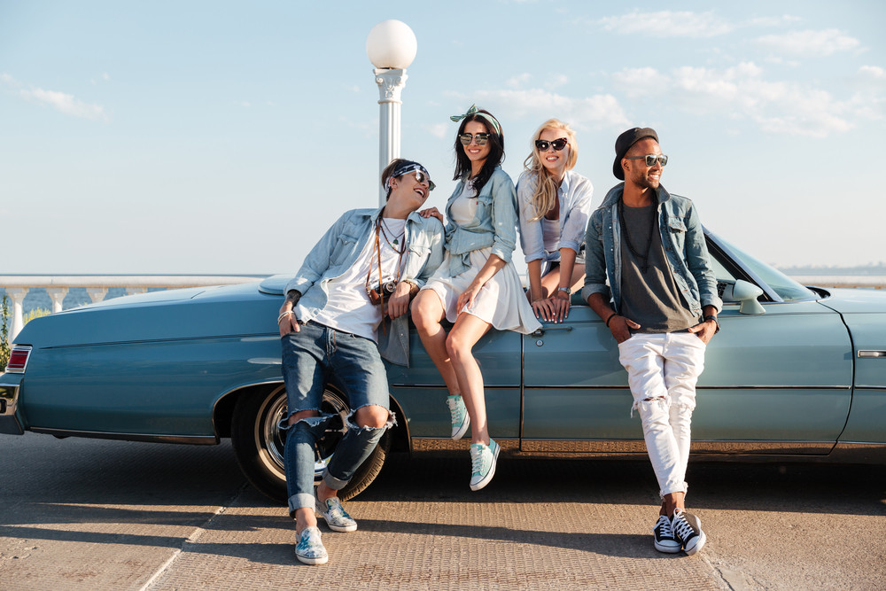 Smiling stylish young friends standing near cabriolet