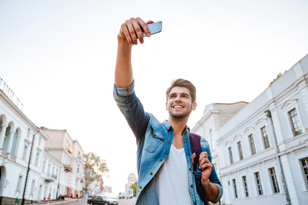 Smiling tourist with backpack making selfies isolated on beautiful modern buildings located in the city centre