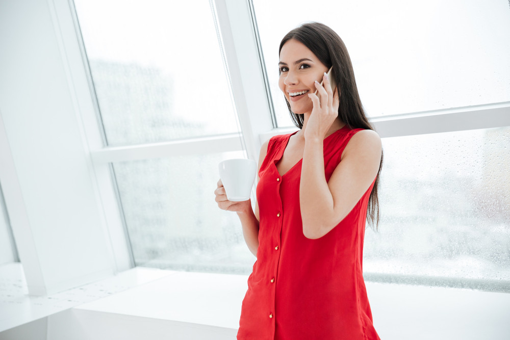 Smiling Woman in red shirt with coffee talking at phone and standing near the window