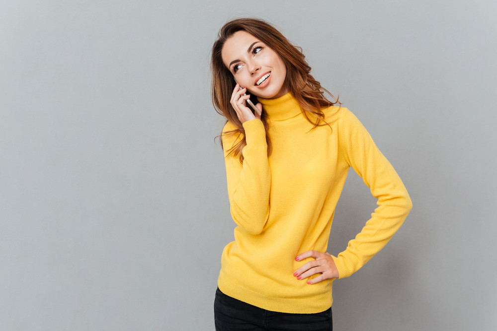 Smiling woman in yellow sweater talking on the phone isolated on a grey background