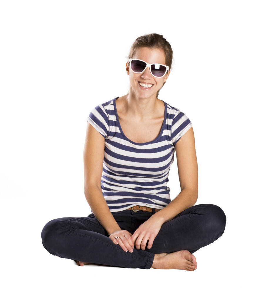 Smiling woman sitting on the floor, studio shot over white.