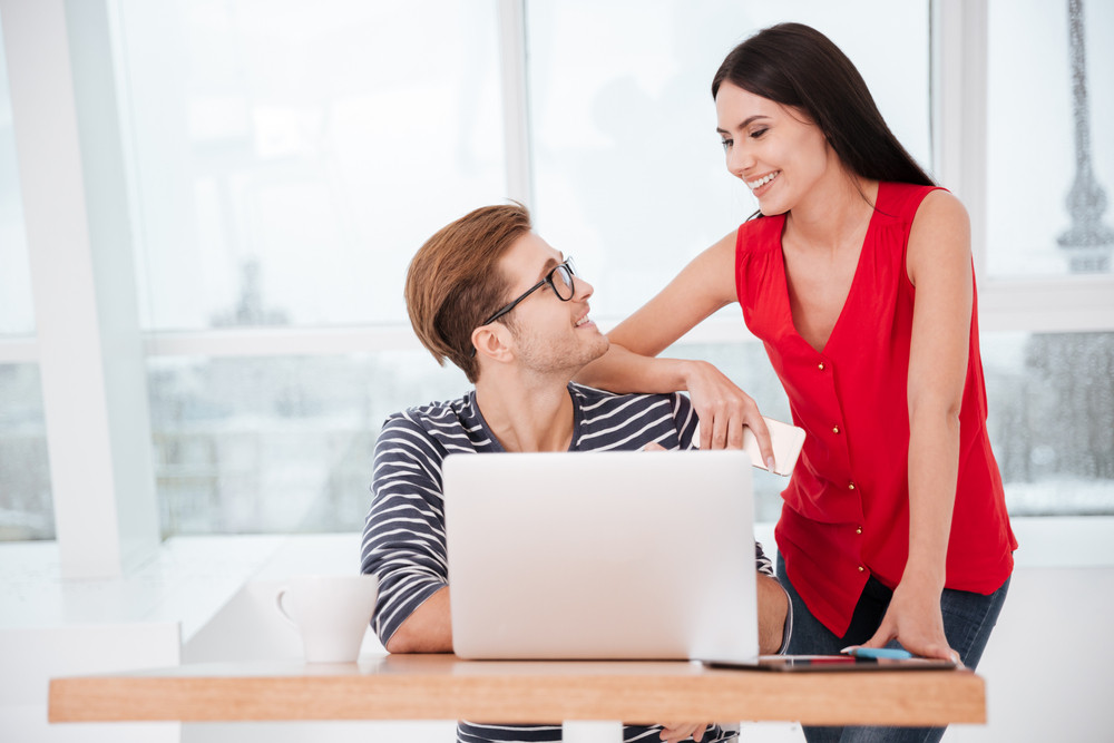 Smiling Woman standing near man which sitting by the table with laptop in office. They looking each other. Window on background