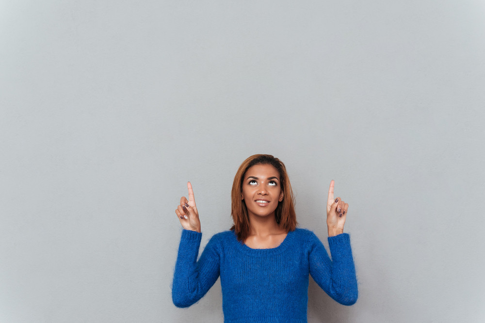 Smiling young african woman in sweater pointing her fingers up and looking up. Girl in studio. Isolated gray background