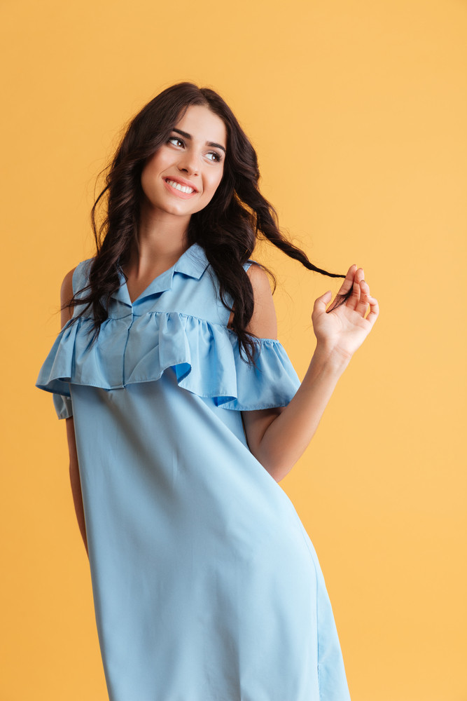 Smiling young brunette woman in blue dress looking away isolated over orange background