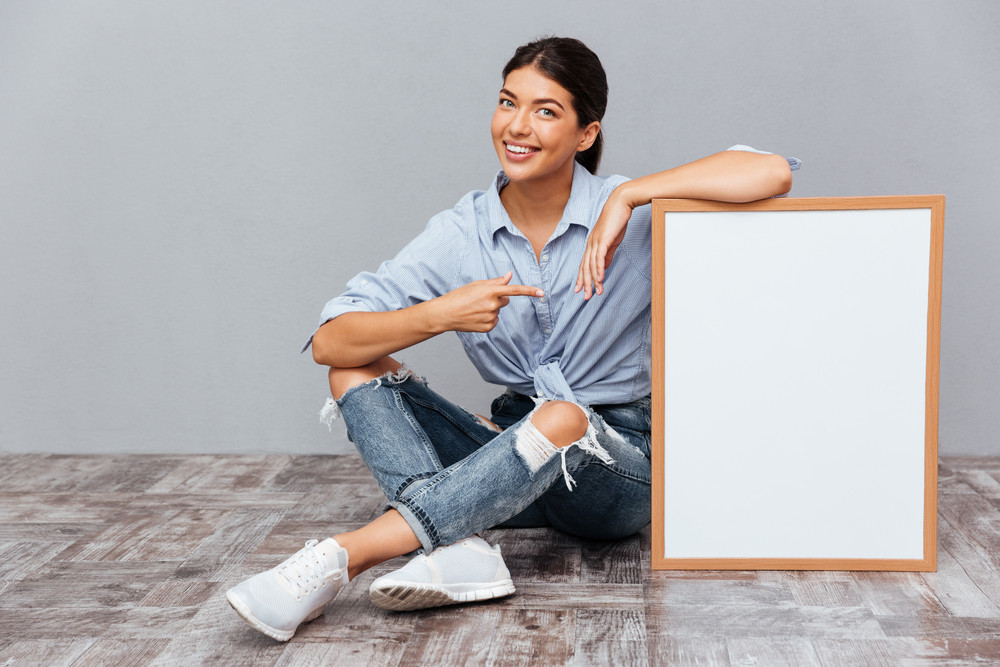 Smiling young brunette woman pointing finger at blank board while sitting on the floor isolated on a gray background