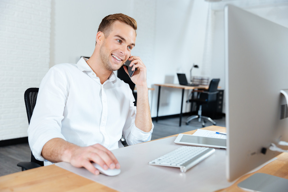 Smiling young businessman working with computer and talking