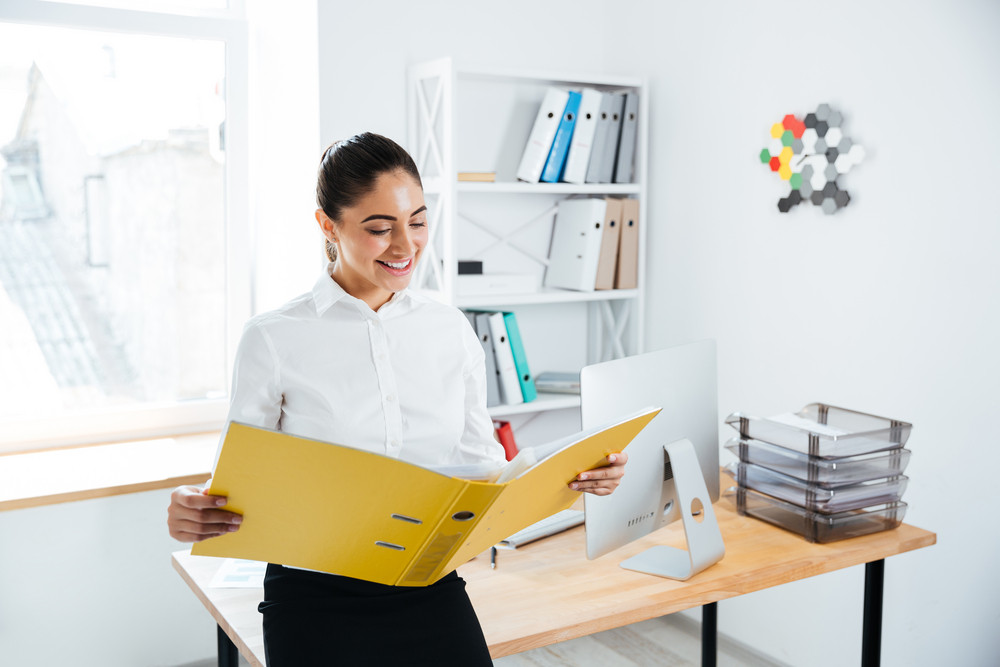 Smiling young businesswoman sitting on the table with documents in office