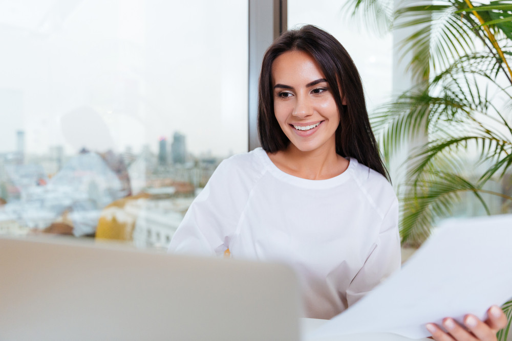 Smiling young businesswoman working with laptop and documents in office