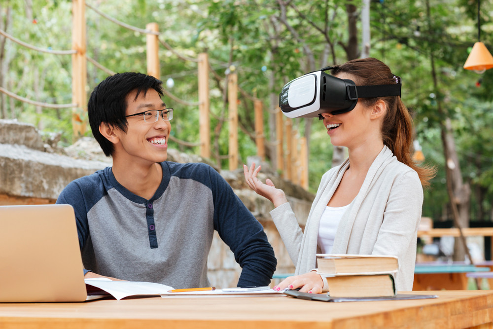 Smiling young couple of student sitting and using virtual reality glasses outdoors