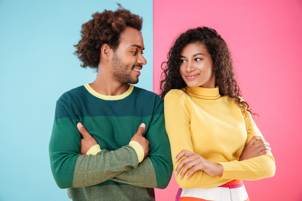 Smiling young couple standing with hands folded and looking at each other