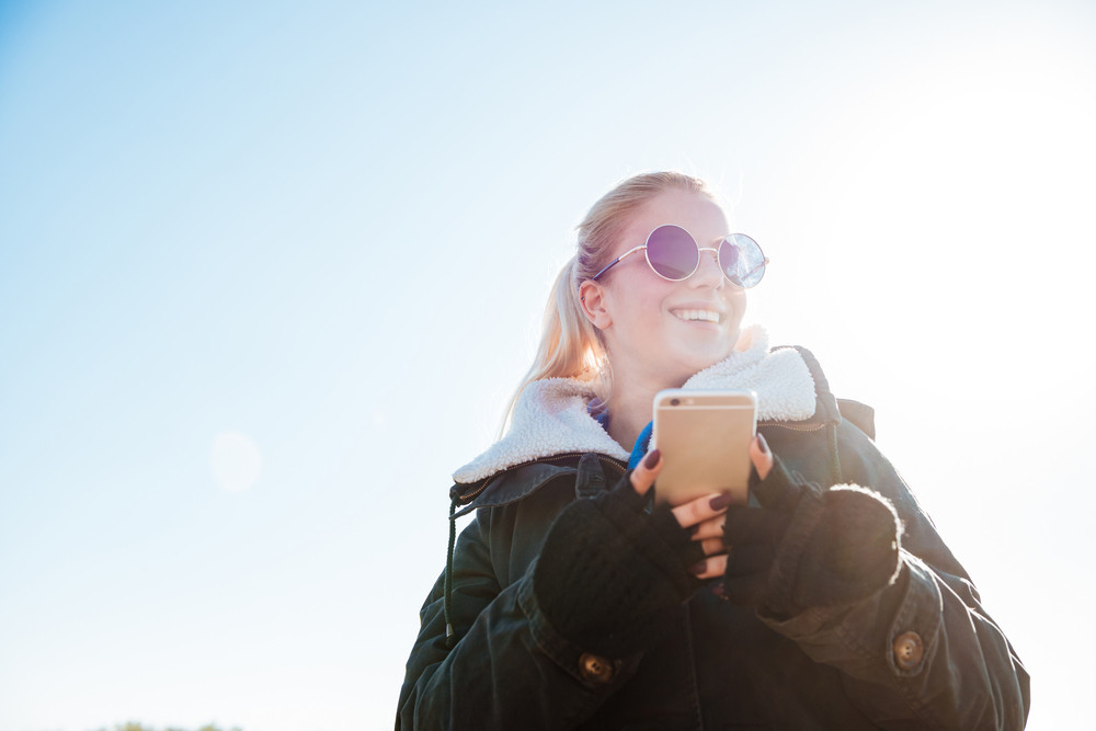 Smiling young girl in jacket holding mobile phone and looking away outdoors