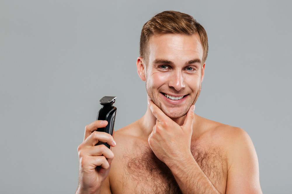 Smiling young handsome man holding razor over gray background
