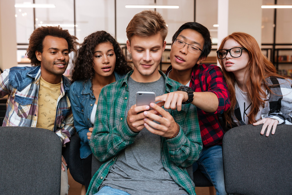 Smiling young man and his friends sitting and using mobile phone together