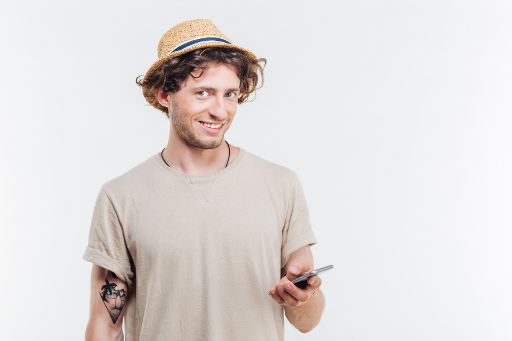 Smiling young man holding smart phone isolated on the white background