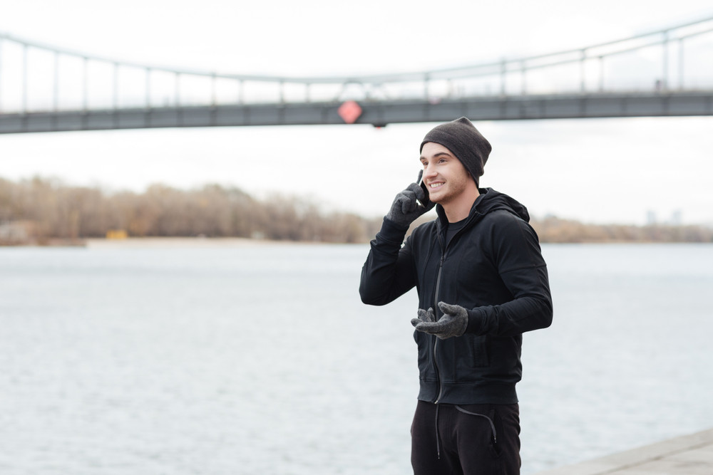 Smiling young man standing and talking on mobile phone near the river