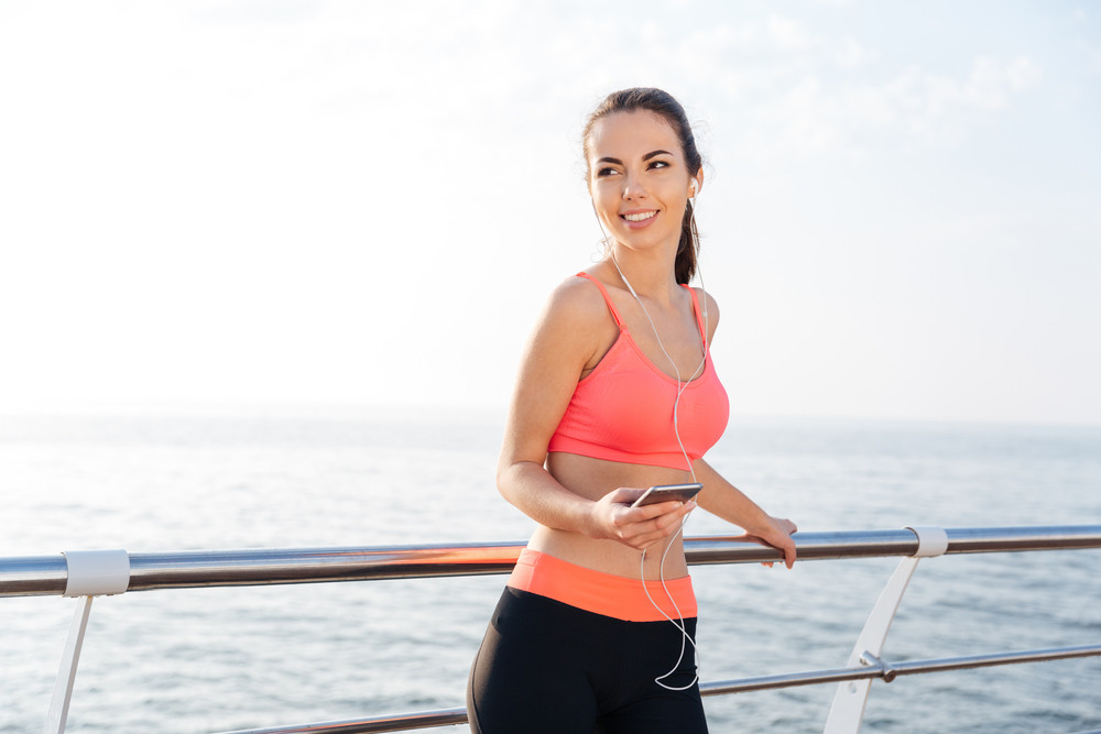 Smiling young sportswoman standing on pier and listening to music from smartphone