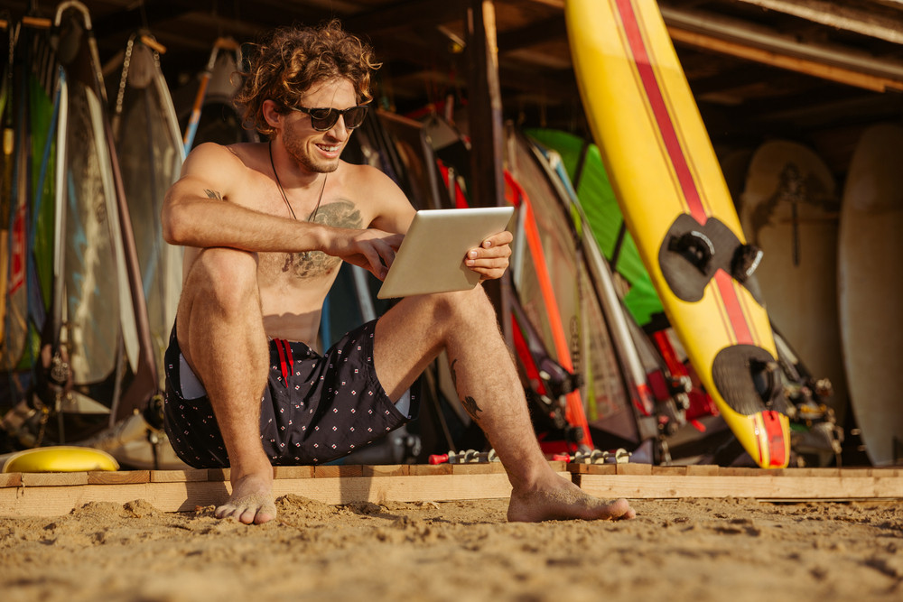 Smiling young surfer man using tablet while sitting on on the beach
