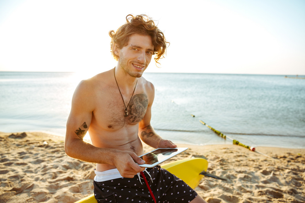 Smiling young surfer man using tablet while sitting on the surf board at the beach