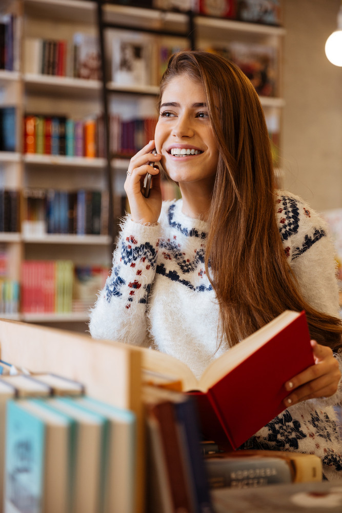 Smiling young woman holding book while talking on the phone in library