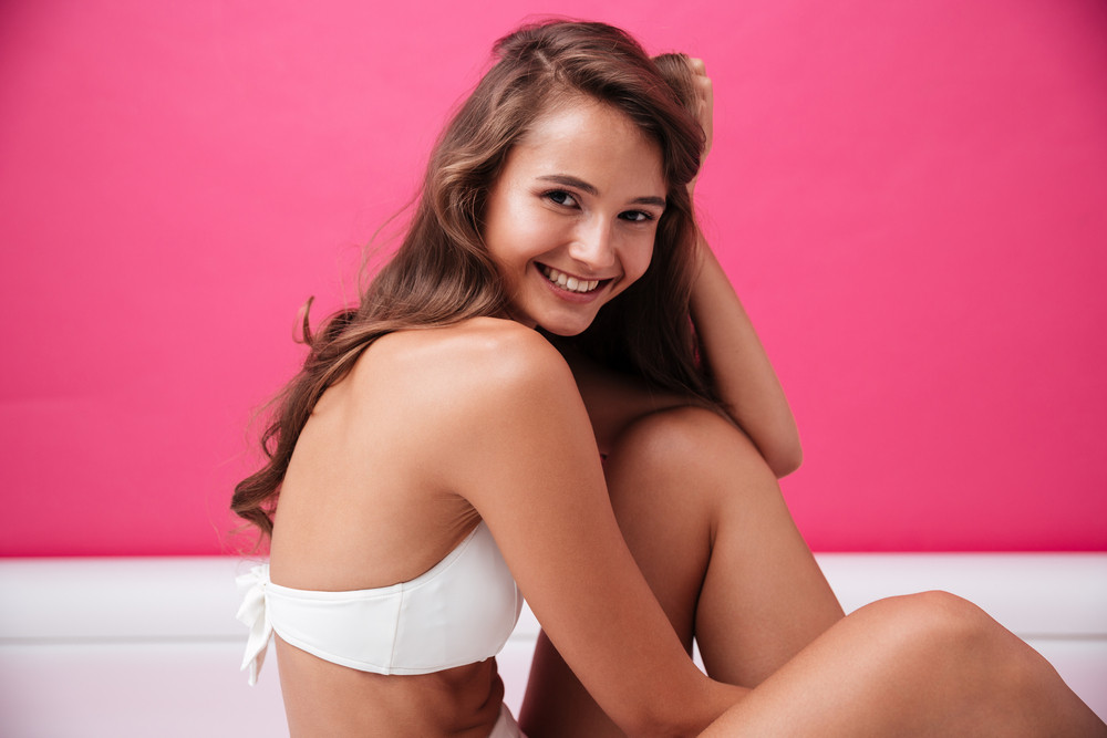 Smiling young woman in white swimsuit looking at camera over pink background