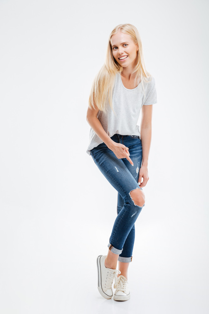 Smiling young woman showing ripped pants isolated on a white background