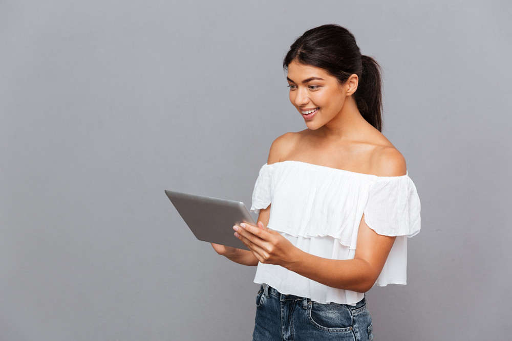 Smiling young woman using tablet computer isolated on a gray background