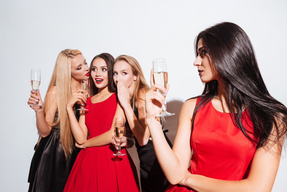 Smiling young women drinking champagne and gossiping on the party over white background