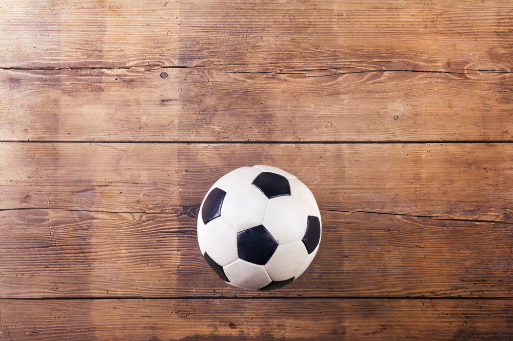 Soccer ball laid on a wooden floor background