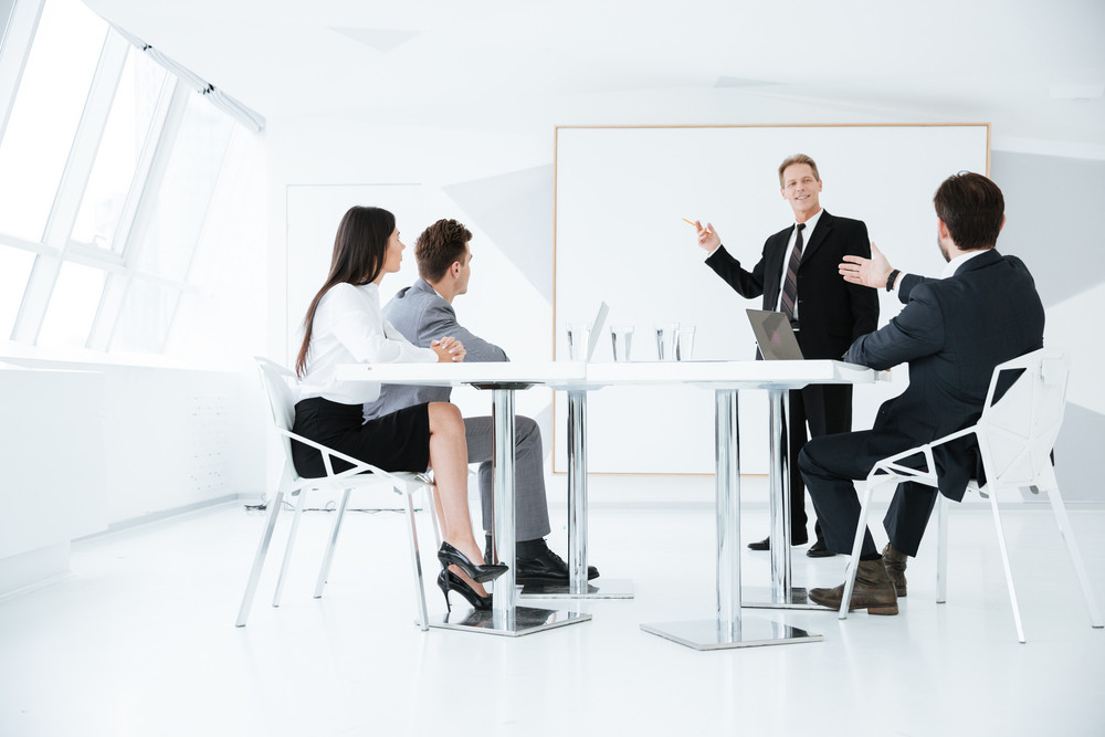 Speech of elderly confident business man which standing near the board on conference with his colleagues which sitting by the table. Full length image