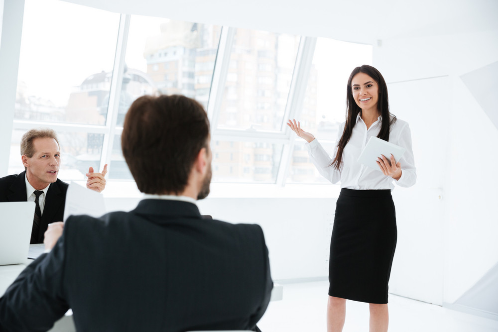 Speech of woman near the board on conference with her collegue which sitting by the table