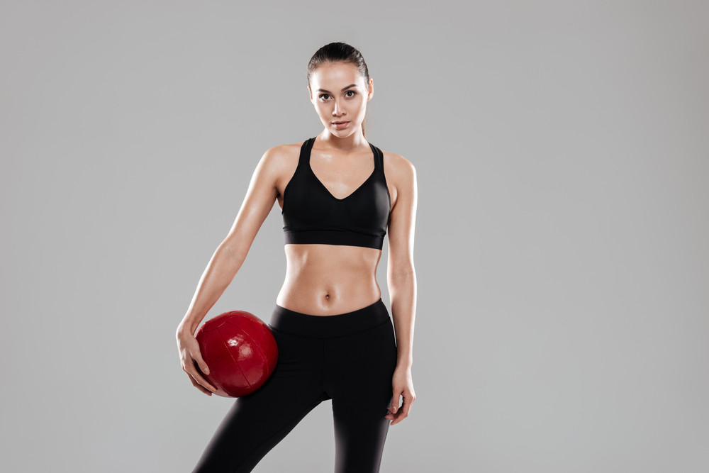 Sporting woman holding ball in hand and looking at camera