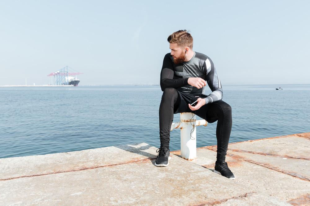 Sportsman sitting near the sea. looking away